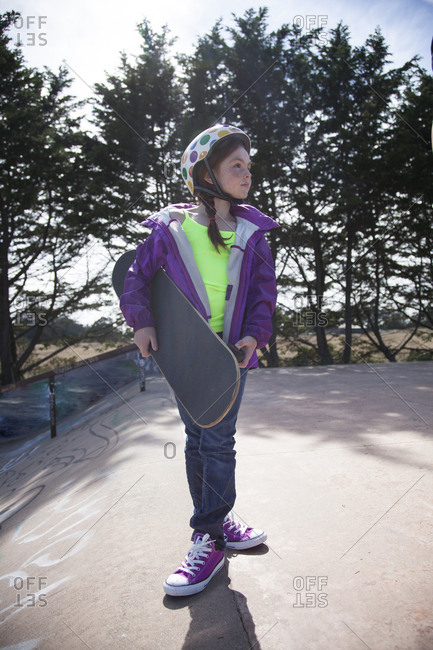 Girl looking away while standing with skateboard at sports ramp