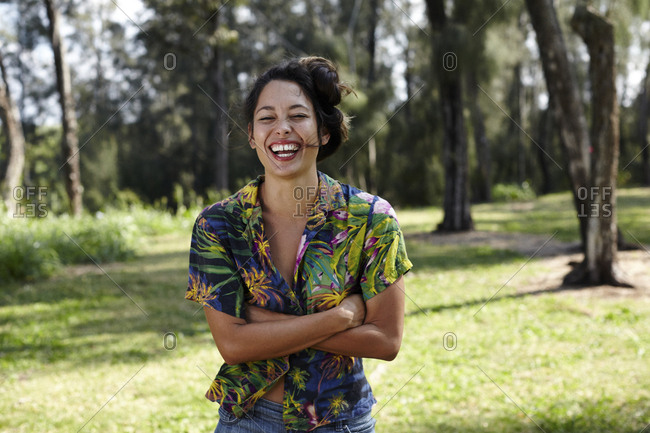 Cheerful woman laughing with arms crossed on grassy field at park
