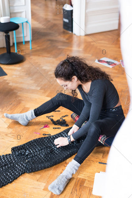 Woman sitting on a floor assembling a costume from black leather