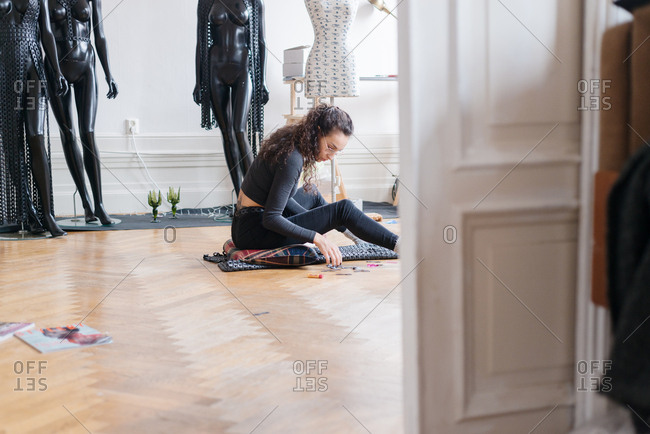 Woman sitting on a floor assembling a black leather costume