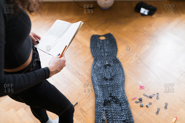 woman creating a costume from pieces of leather woven together