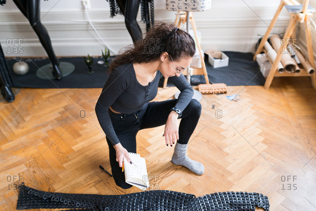 Woman kneeling on a floor looking at an outfit made from leather pieces