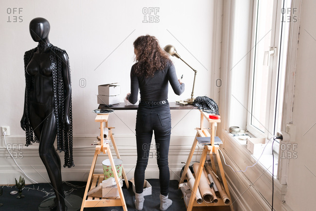 Woman standing in a studio at a makeshift drafting table