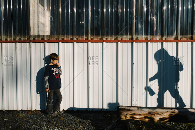 Boy and shadow of child on wall of farm building