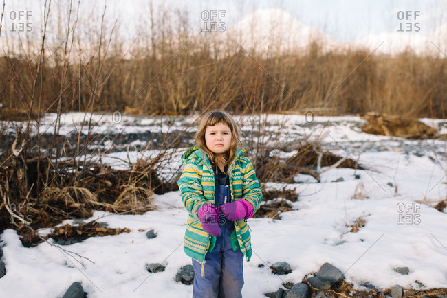 Girl pulling on mittens in winter landscape