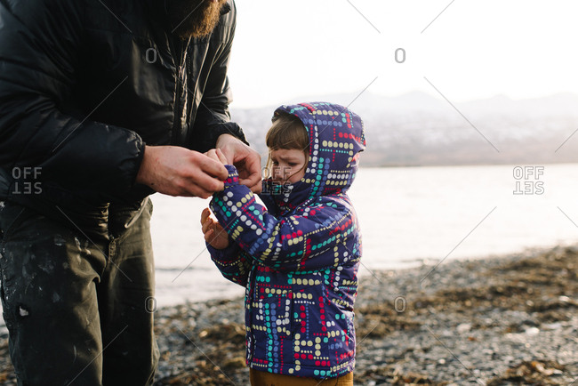 Man helps upset daughter with jacket on beach