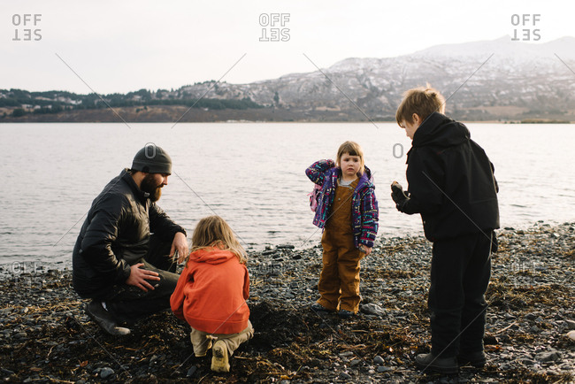Father and three children playing on Alaskan beach