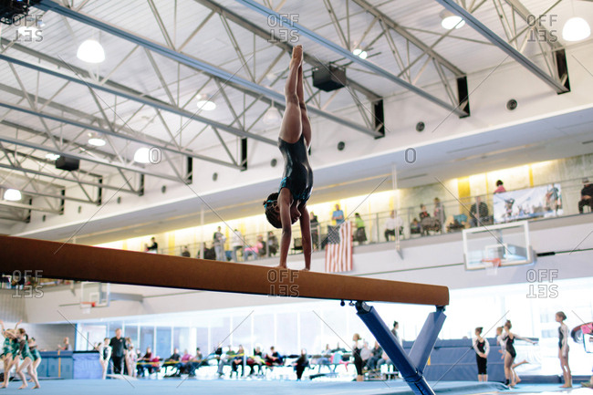 African American girl doing a handstand on a balance beam