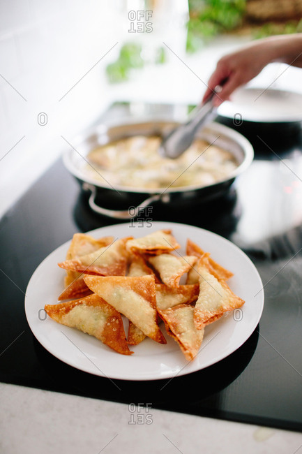 Woman frying wontons at home