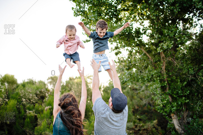 Parents throwing two boys in air
