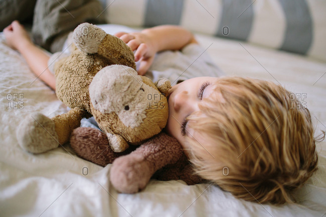 Boy napping with stuffed animals
