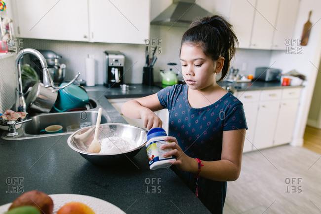 Girl adding ingredient to pancake mix