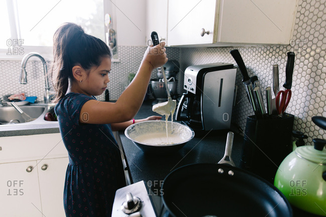 Girl with ladle of pancake mix