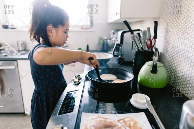 Girl flipping pancakes on stove