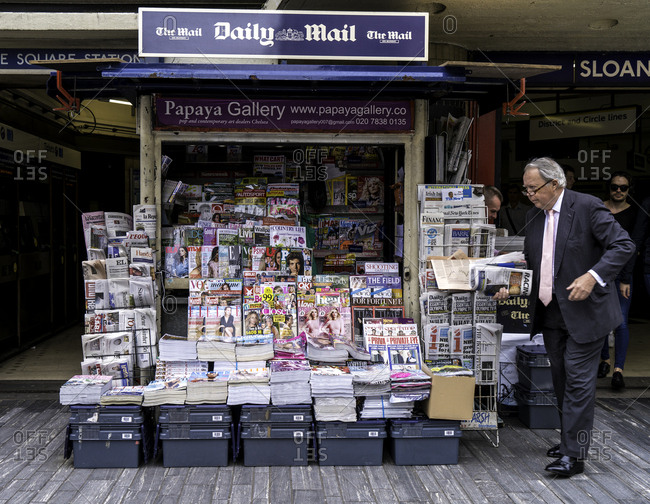 London, England - August 3, 2016: Businessman standing next to a newspaper stand