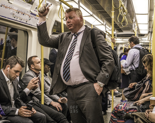 London, England - August 2, 2016: Man standing on a subway surrounded by other passengers