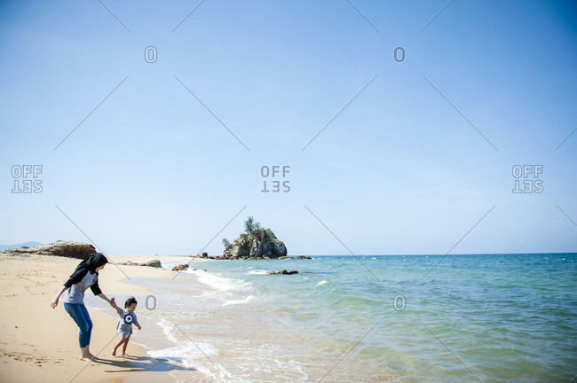 Toddler walking to sea with sister