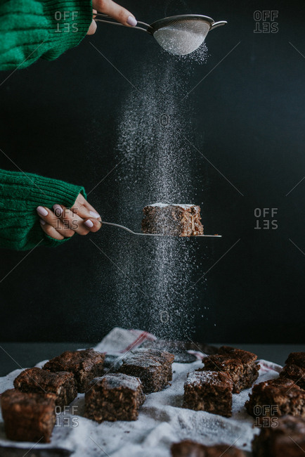 Person sifting confectioner's sugar on homemade vegan brownies