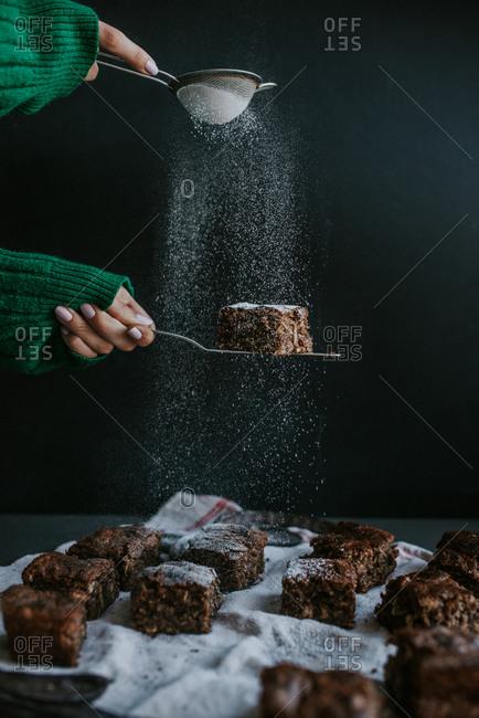 Person dusting powdered sugar on homemade vegan brownies