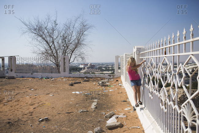 Girl hanging on abandoned fence
