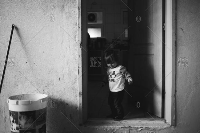 Toddler looking down step of door