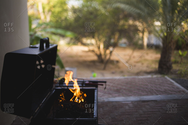 A grill lit on backyard patio