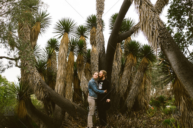Couple standing together in front of a Joshua tree