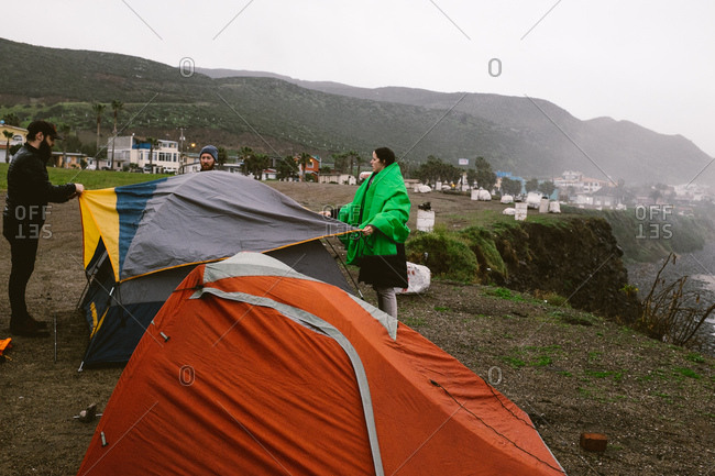 Three friends setting up a campsite on a foggy day