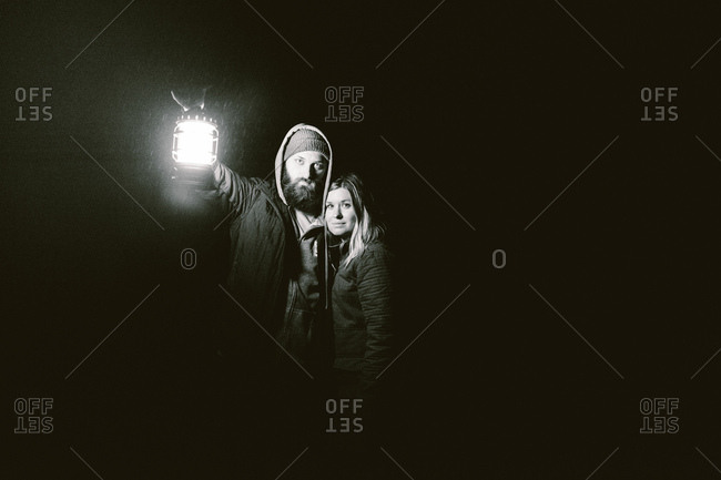 Couple embracing while holding a lantern at night
