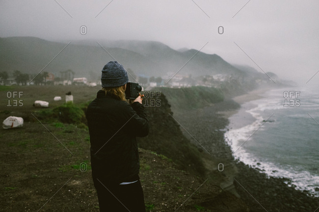 Man taking a super 8 video of the ocean from a cliff