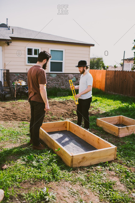 Two men setting up raised garden beds in a backyard