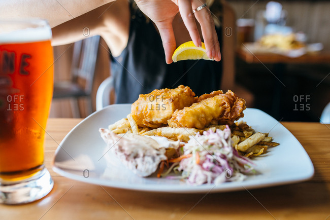 Woman squeezing lemon over fish and chips