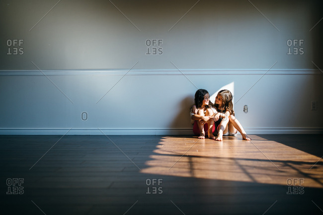Two girls sitting on the floor in an empty living room