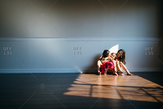 Three girls sitting on the floor in an empty living room