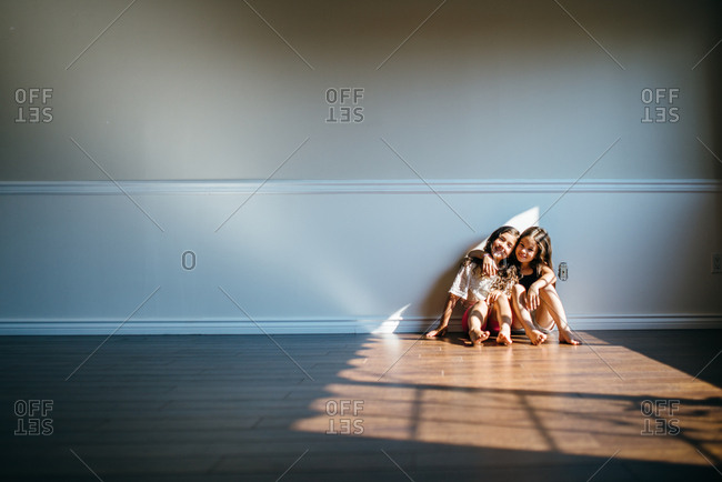 Two girls sitting on the floor hugging in an empty living room