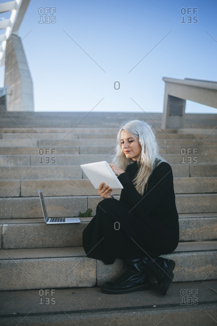 Woman using devices on outdoor steps