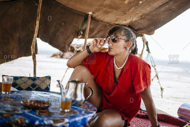 Woman having drink in desert setting