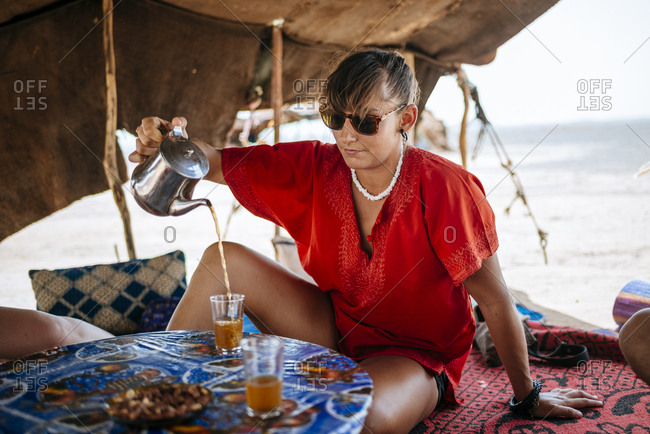 Woman pouring drink in desert setting