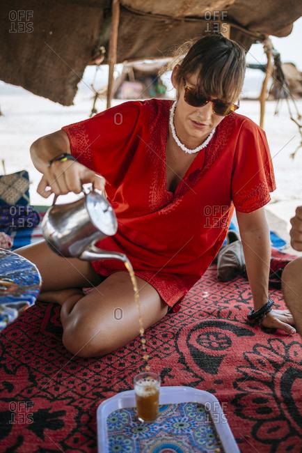 Woman pouring tea in desert setting