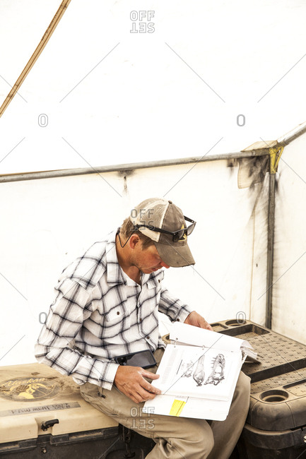 New Mexico - May 16, 2016: Paleontologist reading book in tent