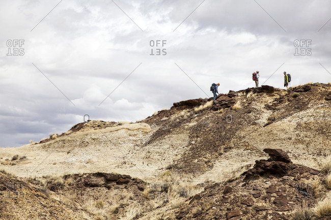 New Mexico - May 16, 2016: Three people walking remote desert hill
