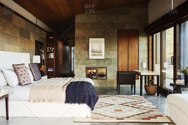 Jackson, Wyoming - October 1, 2016: Master bedroom interior with stone wall and fireplace