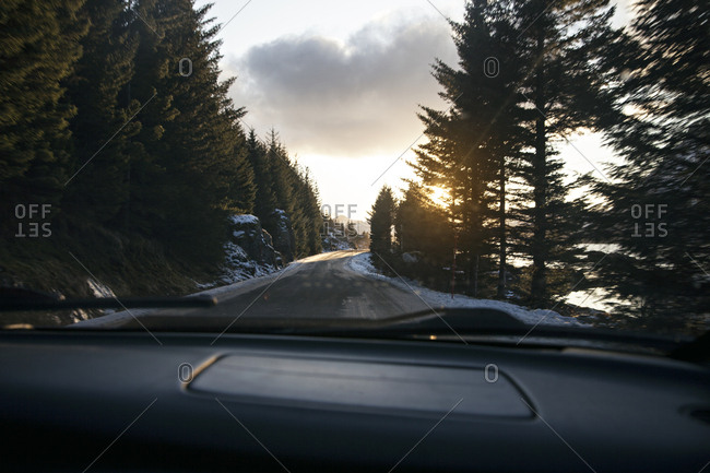 Dashboard of a car driving into the sunset on a mountain road
