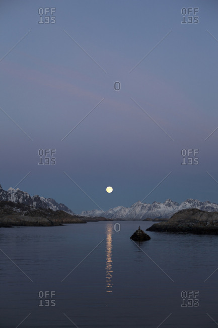 Moon rising over the water and distant mountains in Kabelvag, Norway