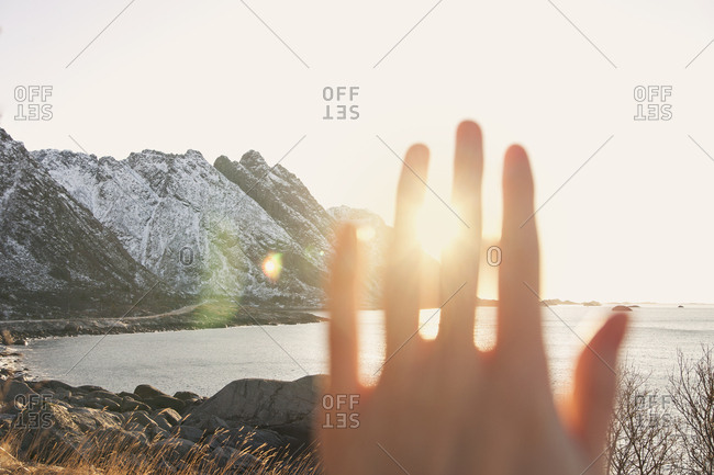 Hand blocking out the sun with a view of distant mountains and water