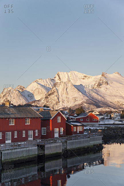 Red fishing houses and distant mountains in Kabelvag, Norway