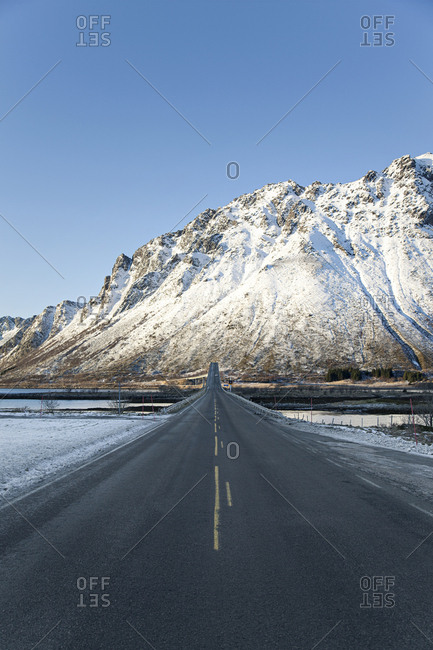 Two-lane highway leading toward a snow-covered mountain in the Lofoten Islands, Norway