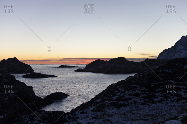 Sun setting over a rocky coastline in Kabelvag, Norway