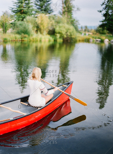 Woman paddling a canoe across a pond