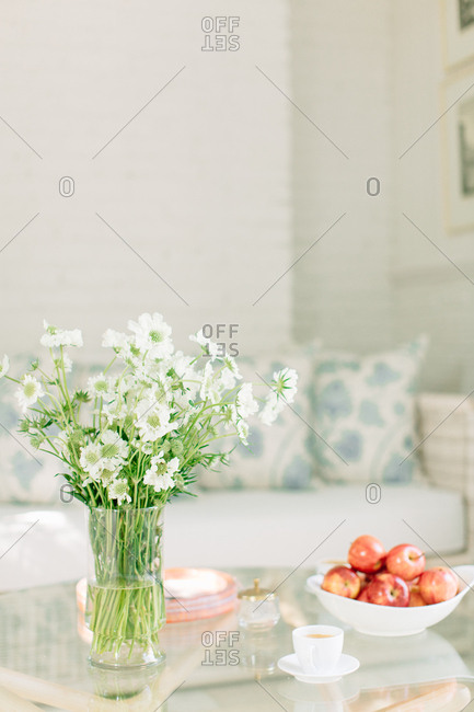 White wildflowers and a bowl of apples on a glass-top table